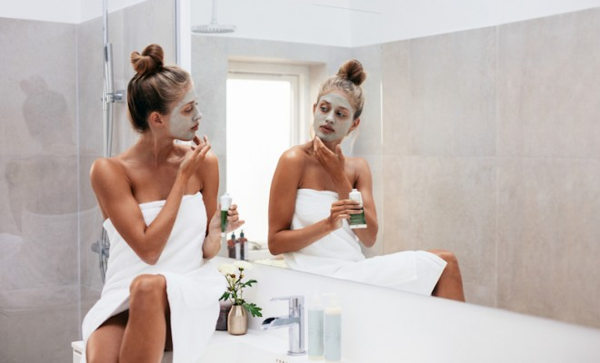 Young-woman-applying-facial-mud-clay-mask-to-her-face-in-bathroom.-Beautiful-female-wrapped-in-towel-looking-into-mirror-and-doing-facial-beauty-treatment.-