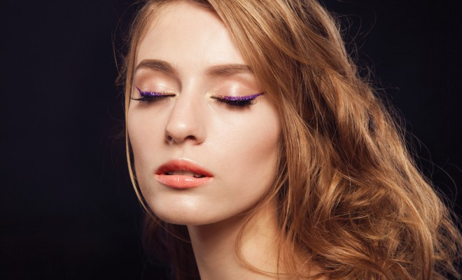 Beautiful woman with bright make up eye with sexy purple sparky gloss liner makeup. Fashion big arrow shape on woman's eyelid. Chic evening make-up, healthy face,curly hair
