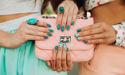 Crop of two women with trendy stylish manicure in mint and bluet tones. female hands holding a pink handbag, fashion accessories, jewelry, large rings with large stones.
