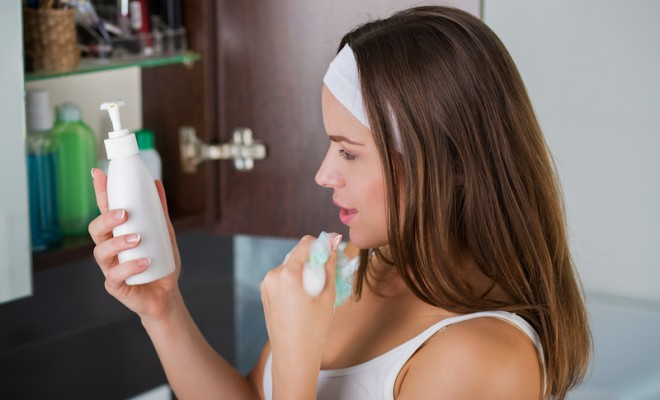 Woman washing up her face with a sponge and a cleanser