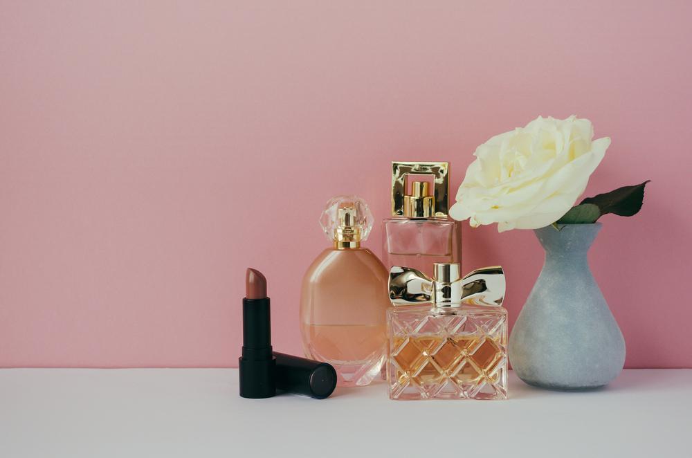 Women's perfume, lipstick, white rose in a vase on the shelf. Minimalist interior
