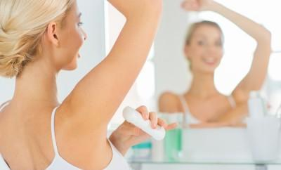 beauty, hygiene, morning and people concept - close up of smiling young woman applying antiperspirant or stick deodorant and looking to mirror at home bathroom