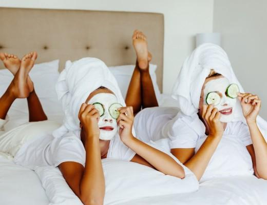 two women with white face masks on with cucumbers
